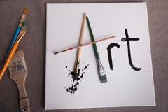 Escovas de pintura brancas da lona a arte da palavra Fotografia de Stock