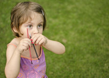 Escovas de pintura da terra arrendada da menina em suas mãos Fotos de Stock