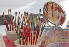 Escovas de pintura das pinturas e das bacias da água usadas para a pintura da cara Foto de Stock
