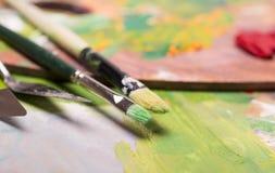 Escovas de pintura do artista, pintura de óleo no backg artístico de madeira da paleta Imagem de Stock