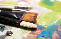 Escovas de pintura do artista e pintura de óleo na paleta artística de madeira b Fotos de Stock