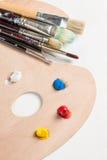 Escovas de pintura e pintura em um paletter Fotos de Stock