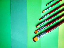 Escovas de pintura em um fundo do papel colorido foto de stock