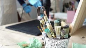 Escovas de pintura em uma cubeta O artista prepara uma imagem vídeos de arquivo