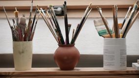 Escovas de pintura no frasco que está em um peitoril da janela vídeos de arquivo