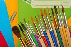 Escovas de pintura no fundo do livro de exercício Foco seletivo Foto de Stock