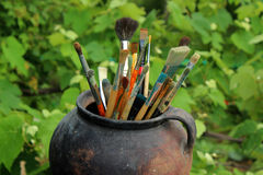 Escovas de pintura no potenciômetro velho Fotografia de Stock Royalty Free