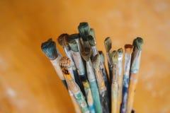 Escovas de pintura no vaso em uma tabela de madeira, clouse-up Fotografia de Stock Royalty Free