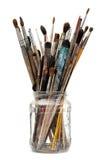 Escovas de pintura sujas Assorted na garrafa de vidro imagem de stock