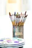Escovas de pintura velhas no latas Foto de Stock