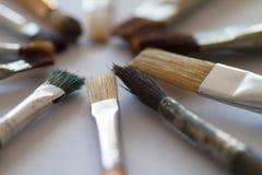 Escovas do artista em uma tabela branca Fotografia de Stock Royalty Free