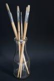 Escovas do artista no frasco de leite velho Imagens de Stock