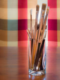 Escovas do artista no vidro alto Fotos de Stock Royalty Free