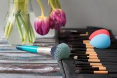 Escovas e esponjas cosméticas profissionais em uma tabela de madeira imagem de stock