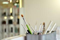 Escovas e ferramentas para o tratamento de mãos e o nailart no vidro branco no salão de beleza no fundo de um espelho e de umas a fotografia de stock