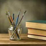 Escovas e livros de pintura Fotos de Stock Royalty Free