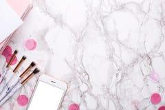 Escovas e telefone celular cosméticos em um fundo de mármore fotografia de stock royalty free