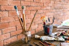 Escovas e tubos com pinturas na tabela de madeira na oficina do artista fotografia de stock royalty free