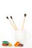 Escovas em uma caneca com pinturas Fotos de Stock Royalty Free