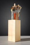 Escovas para pintar em um vidro de madeira imagens de stock