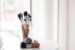 Escovas profissionais da composição em um vidro Foto de Stock