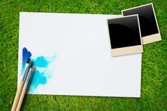 Escove e forre com a foto do frame na grama Imagem de Stock Royalty Free
