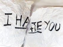 Escríbame LE ODIAN en el papel Imagen de archivo libre de regalías