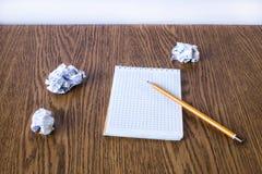 Escreva, caderno limpo e diversas folhas amarrotadas Fotografia de Stock