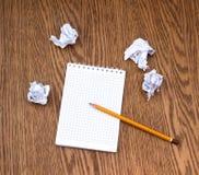 Escreva, caderno limpo e diversas folhas de papel amarrotadas Fotografia de Stock Royalty Free