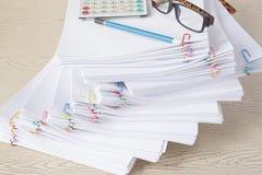 Escreva com espetáculos e calculadora na pilha de papel da sobrecarga Fotografia de Stock Royalty Free