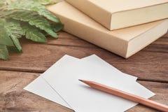 Escreva com papel e livro na tabela de madeira fotografia de stock royalty free