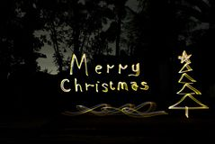 Escreva cumprimentos do Natal com luzes douradas na noite foto de stock royalty free