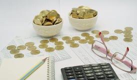 Escreva no caderno e nos espetáculos com as moedas postas como o dinheiro Fotografia de Stock