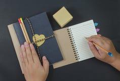 Escreva os lápis de papel do caderno no fundo preto imagem de stock