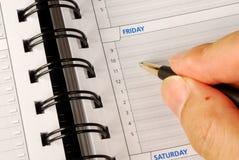 Escreva para baixo o que fazer no planejador do dia imagem de stock