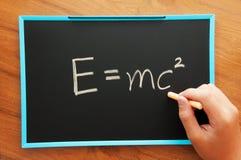 Escrevendo a fórmula física fotos de stock