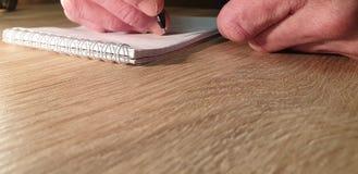 Escrevendo a mão no close-up do caderno Escrita em um caderno imagens de stock royalty free