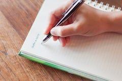 Escrevendo a nota importante no caderno espiral Fotografia de Stock Royalty Free