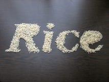Escrevendo o arroz da palavra com sementes do arroz em uma tabela com fundo de madeira marrom imagem de stock