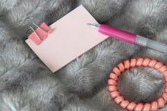 Escrevendo a pena cor-de-rosa em claro - etiqueta cor-de-rosa com artigos de papelaria cor-de-rosa da braçadeira do metal fotografia de stock