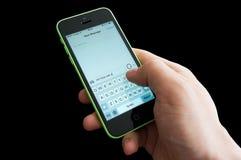 Escrevendo SMS em uma tela do iphone Fotos de Stock