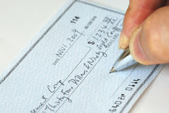 Escrevendo uma verificação à conta de pagamento Fotos de Stock
