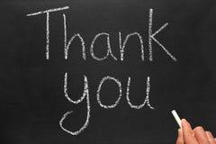Escrever agradece-lhe em um quadro-negro. Fotos de Stock