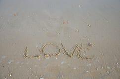 Escriba el amor de la palabra en la playa Fotos de archivo