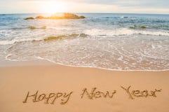 Escriba la Feliz Año Nuevo en la playa Imagenes de archivo