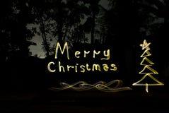 Escriba los saludos de la Navidad con las luces de oro en la noche foto de archivo libre de regalías
