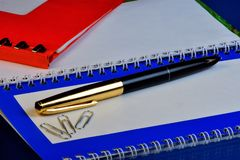 Escriba un plan o un informe en un cuaderno, carpeta, pluma de los efectos de escritorio imagen de archivo libre de regalías