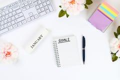 Escriba una meta por el Año Nuevo 2010 en un cuaderno blanco en una mesa blanca al lado de una taza de café y de un teclado Visió foto de archivo