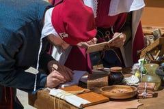Escribanos medievales que escriben caligrafía Imagen de archivo libre de regalías