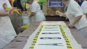 Escribe una inscripción en la torta, la empanada grande para el cumpleaños o la boda, el trabajo del confitero, el cocinero en gu metrajes